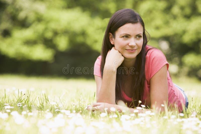 Mujer que miente al aire libre sonriendo imagen de archivo