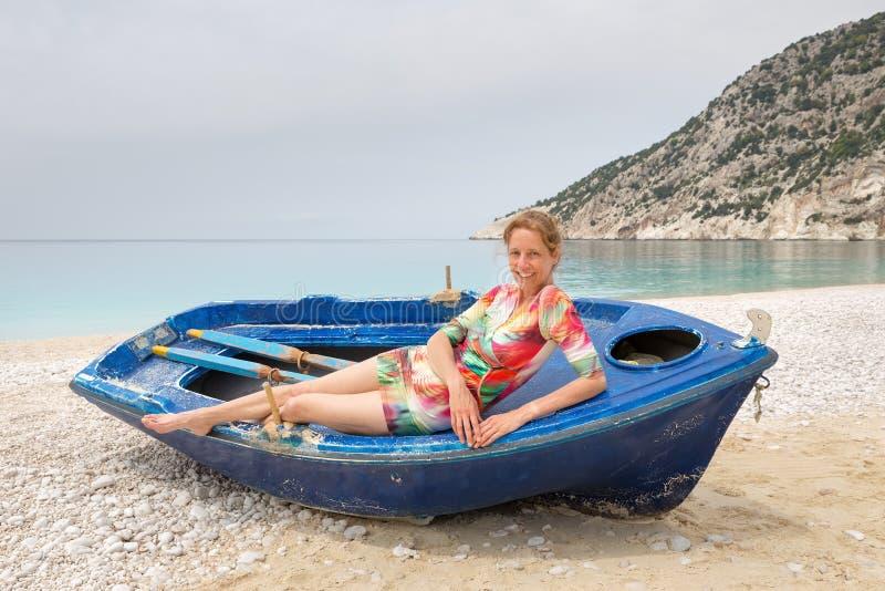 Mujer que miente en barco de rowing en la playa griega imagen de archivo libre de regalías