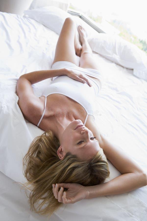 Mujer que miente en cama imágenes de archivo libres de regalías