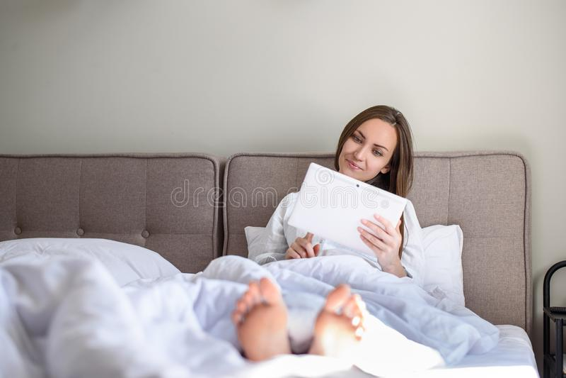 Mujer que miente en cama debajo de la manta en la tableta, navegación por Internet, noticias, buena mañana fotos de archivo libres de regalías
