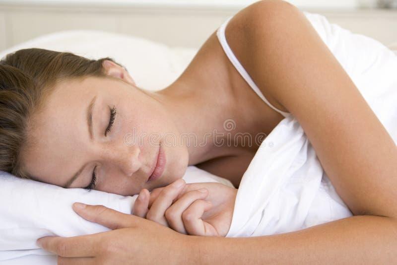 Mujer que miente en dormir de la cama imagenes de archivo