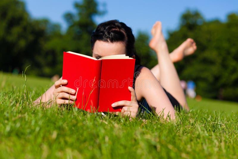 Mujer que miente en el libro de lectura de la hierba foto de archivo libre de regalías