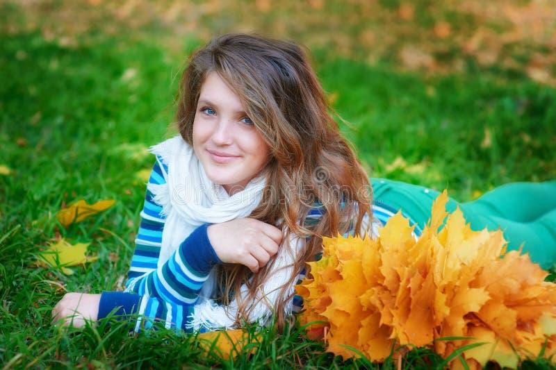 Mujer que miente en el retrato al aire libre de las hojas de otoño en parque fotos de archivo