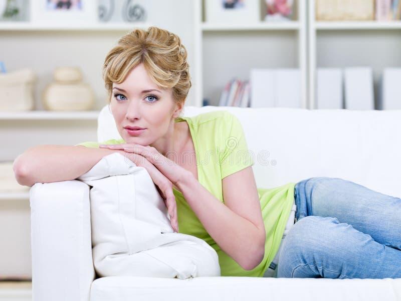 Mujer que miente en el sofá imagenes de archivo
