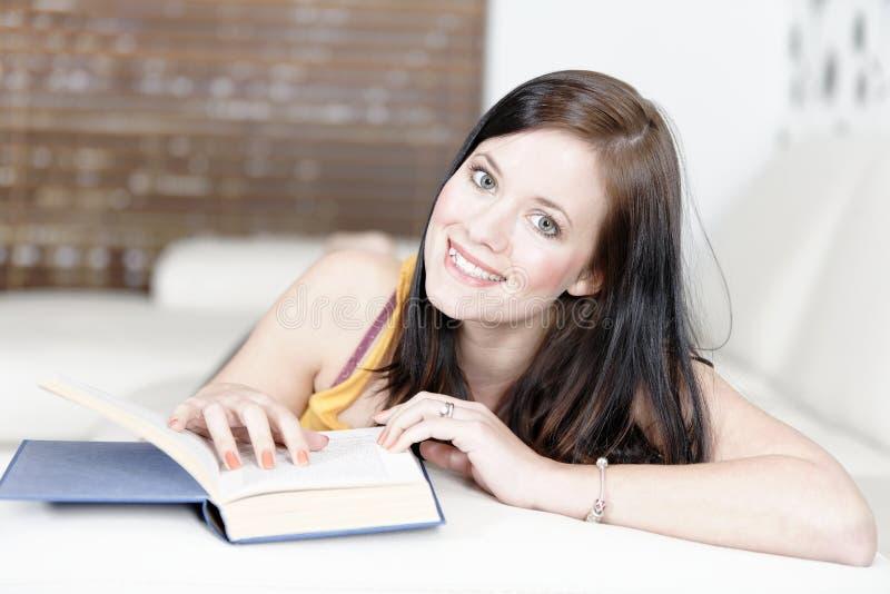Mujer que miente en el sofá con un libro imagenes de archivo