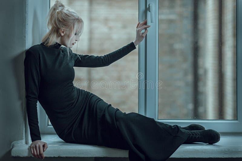 Mujer que miente en el travesaño de la ventana y triste fotos de archivo
