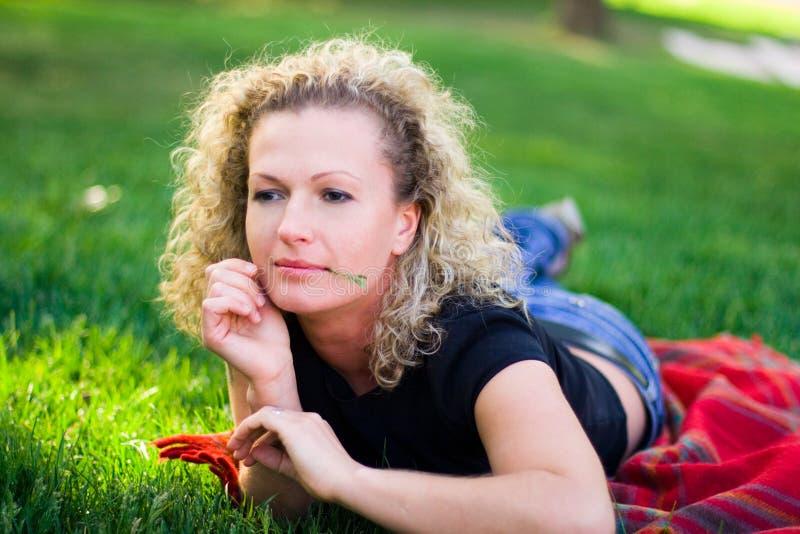 Mujer que miente en hierba verde fotos de archivo