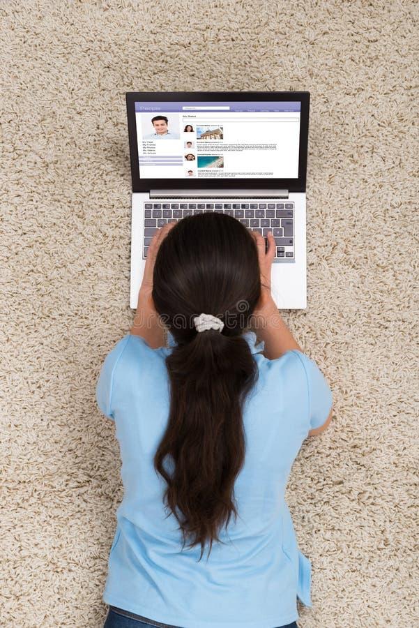 Mujer que miente en la alfombra con el ordenador portátil fotos de archivo libres de regalías