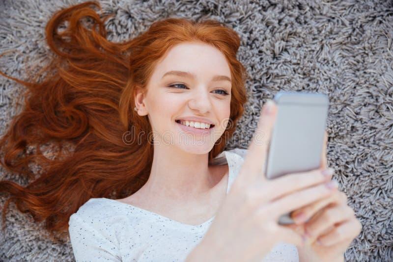 Mujer que miente en la alfombra y que usa smartphone imagen de archivo