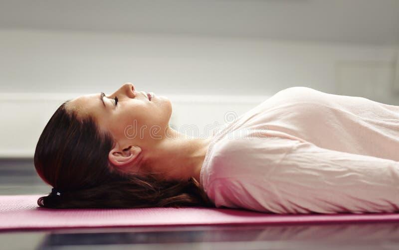 Mujer que miente en la estera de la yoga que se relaja los músculos imágenes de archivo libres de regalías