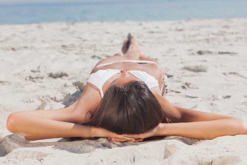 Mujer que miente en la playa delante del océano fotografía de archivo libre de regalías