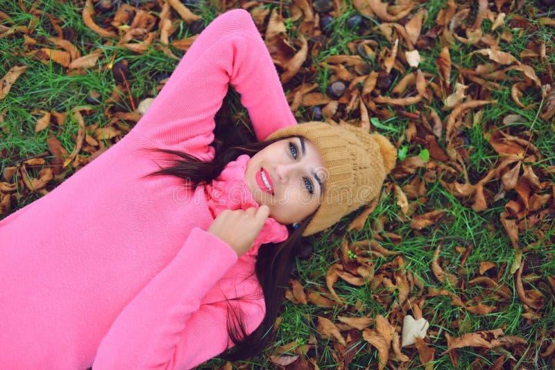 Mujer que miente en las hojas de otoño fotos de archivo libres de regalías