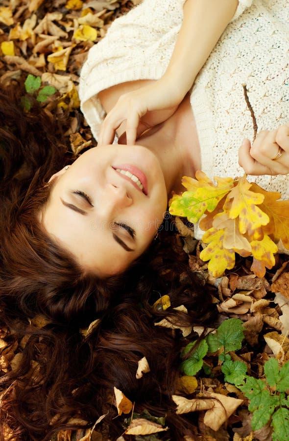 Mujer que miente en las hojas de otoño, retrato al aire libre fotos de archivo libres de regalías