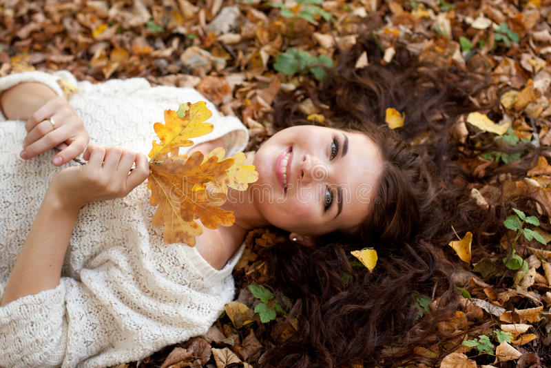 Mujer que miente en las hojas de otoño, retrato al aire libre fotos de archivo