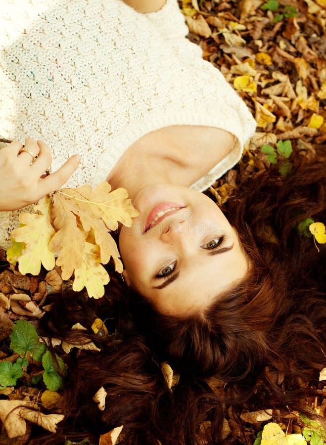 Mujer que miente en las hojas de otoño, retrato al aire libre imagen de archivo