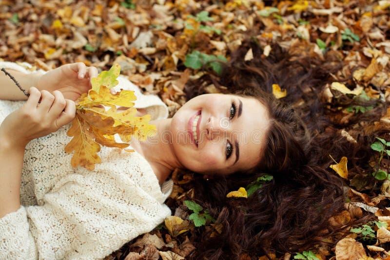 Mujer que miente en las hojas de otoño, retrato al aire libre fotografía de archivo
