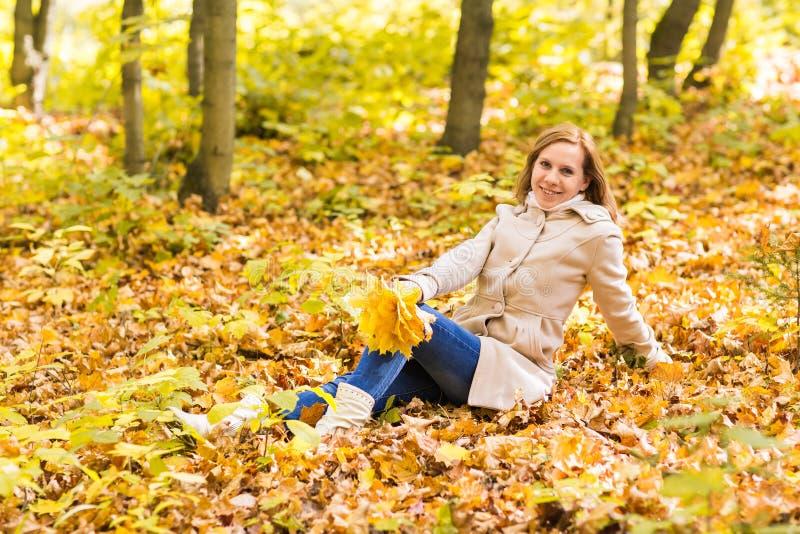 Mujer que miente en las hojas de otoño, retrato al aire libre foto de archivo libre de regalías