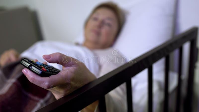 Mujer que miente en lecho de enfermo y los canales que cambian en TV, sala personal en hospital fotografía de archivo