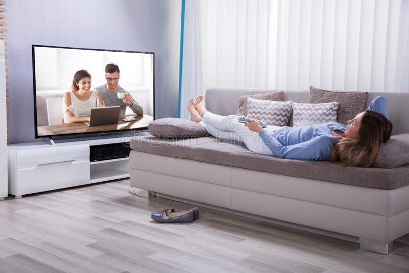 Mujer que miente en Sofa Watching Television foto de archivo libre de regalías