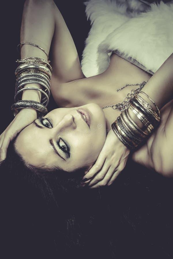 Download Mujer Que Miente Y Sensual Con Las Pulseras Del Oro Y De La Plata, Verdes Imagen de archivo - Imagen de joyería, maquillaje: 44852155