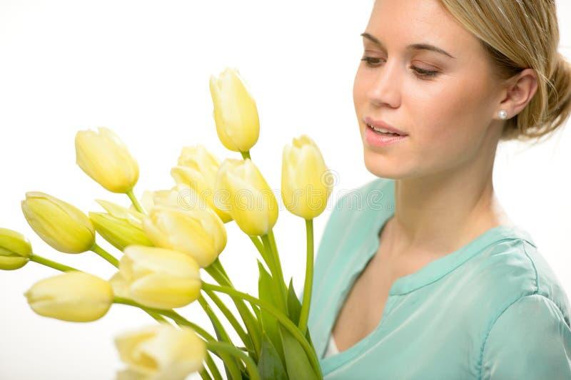 Mujer que mira abajo de las flores amarillas de la primavera del tulipán fotos de archivo