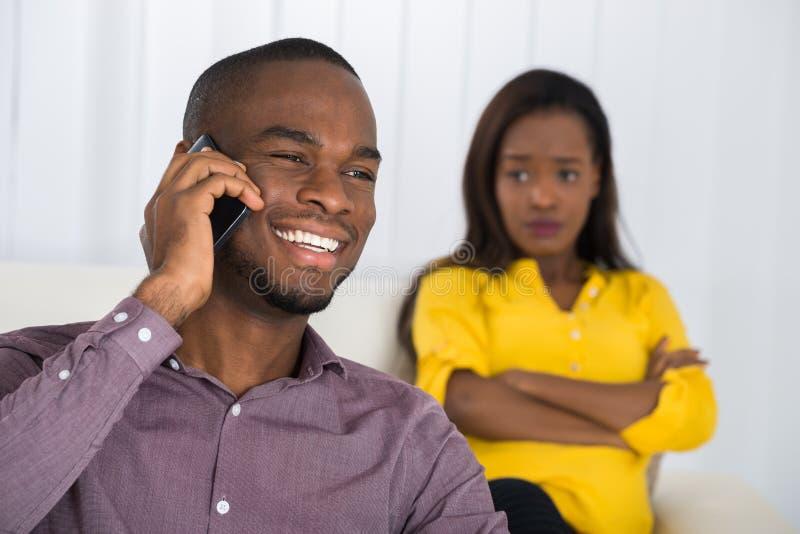 Mujer que mira al hombre que habla en el teléfono móvil foto de archivo