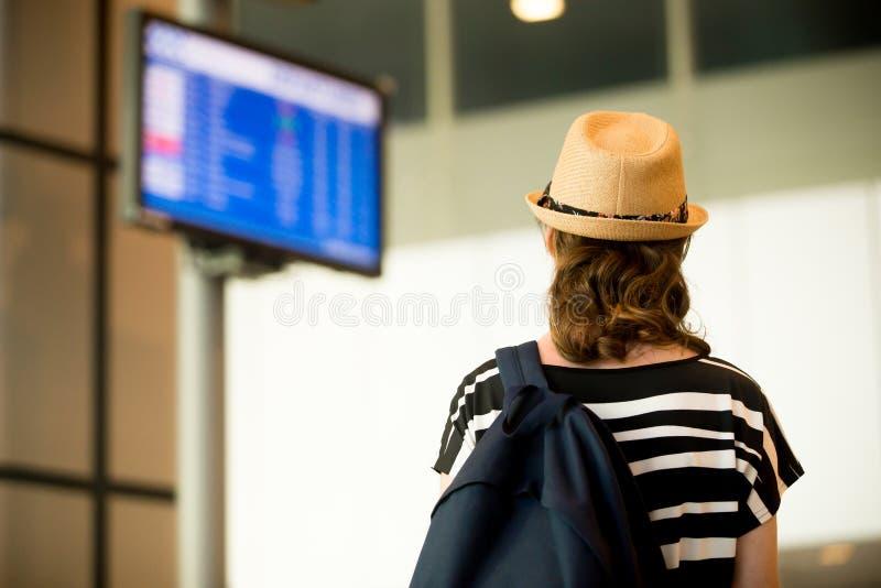 Mujer que mira al tablero de la información del vuelo del aeropuerto imagen de archivo