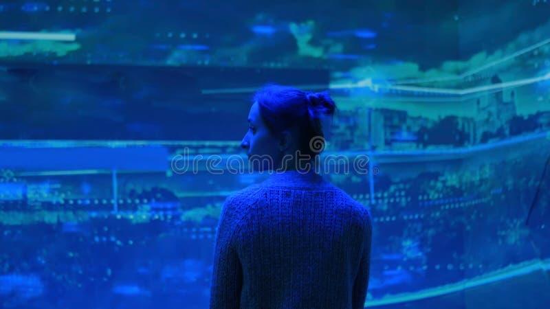 Mujer que mira alrededor y presentación video de observación en la pared grande de la exhibición imágenes de archivo libres de regalías
