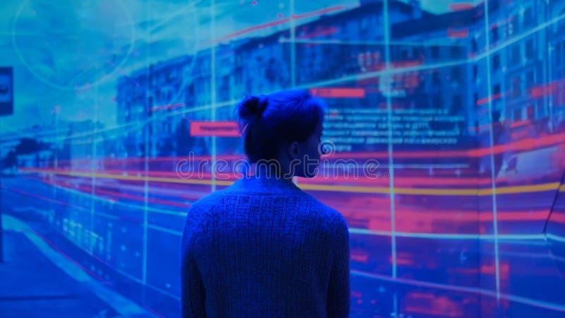 Mujer que mira alrededor y presentación video de observación en la pared grande de la exhibición foto de archivo libre de regalías