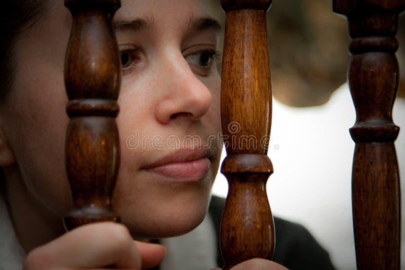 Mujer que mira con fijeza a través de los pasamanos de la escalera imagen de archivo