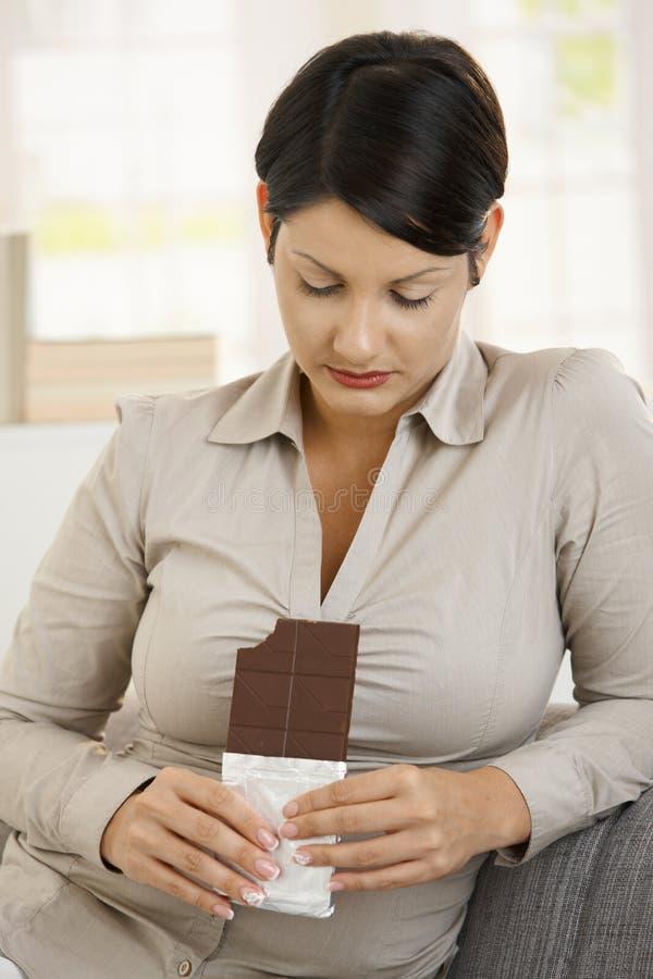 Mujer que mira culpable al chocolate foto de archivo libre de regalías