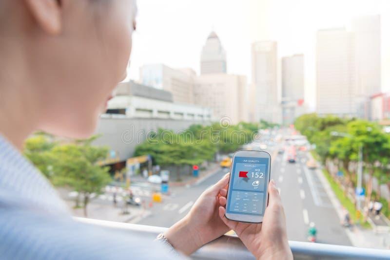Mujer que mira el índice app de la calidad del aire fotos de archivo