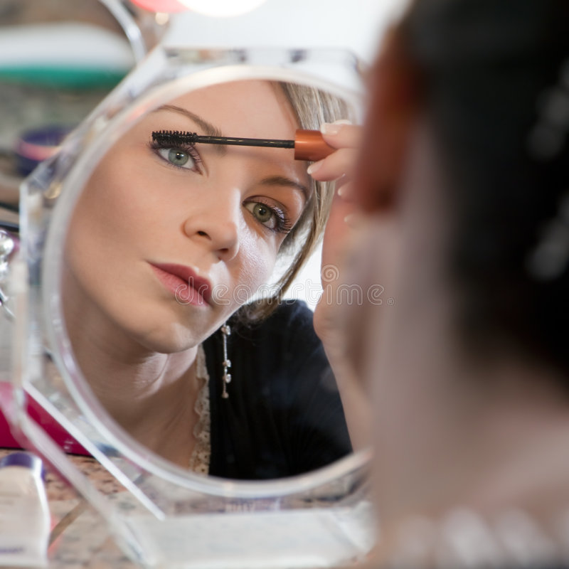 Mujer que mira el espejo foto de archivo