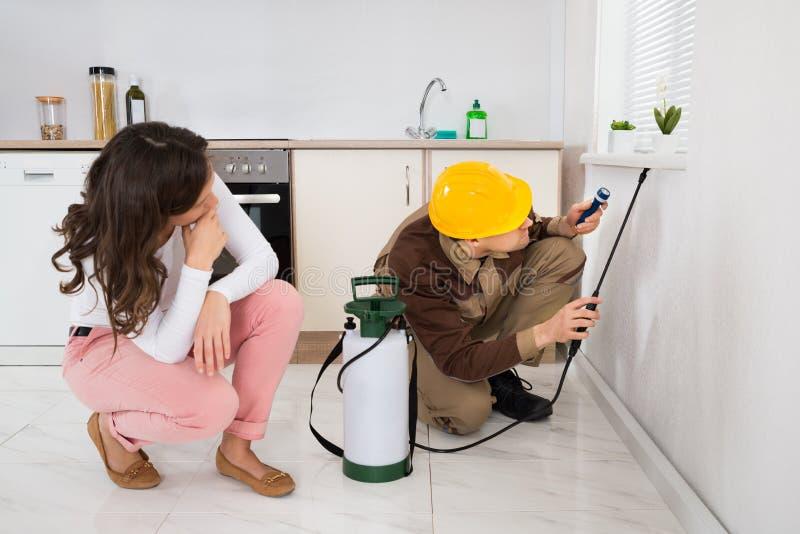 Mujer que mira el insecticida de rociadura del trabajador debajo de alféizar foto de archivo libre de regalías