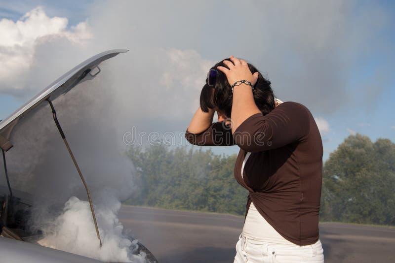 Mujer que mira el motor de coche que fuma imagenes de archivo