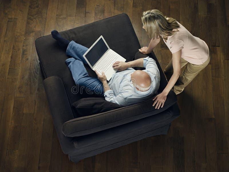 Mujer que mira el ordenador portátil calvo del uso del hombre fotografía de archivo