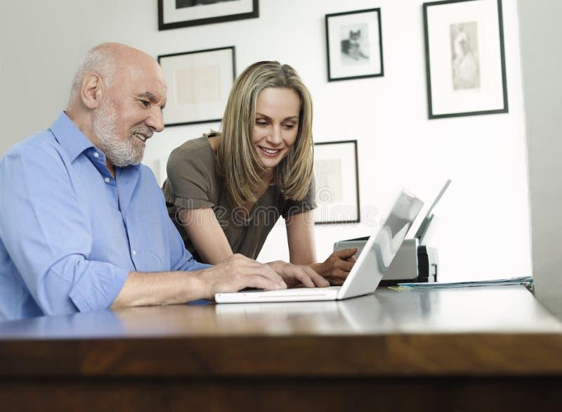 Mujer que mira el ordenador portátil maduro del uso del hombre en casa foto de archivo libre de regalías