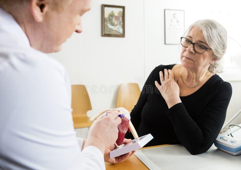 Mujer que mira el puño masculino MES del doctor Explaining Shoulder Rotator imagen de archivo