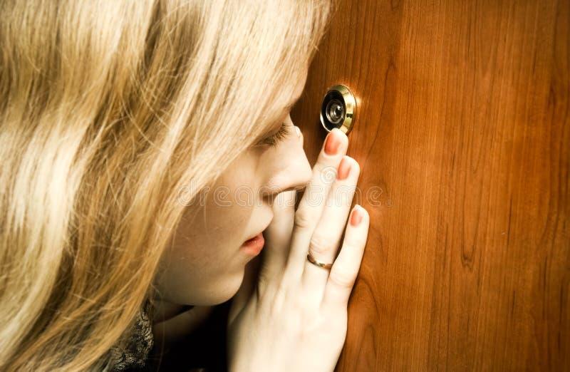 Mujer que mira en el agujero del espía imagen de archivo libre de regalías
