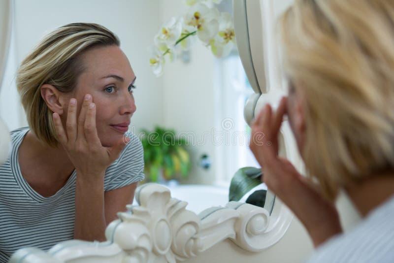 Mujer que mira en el espejo del cuarto de baño fotografía de archivo libre de regalías