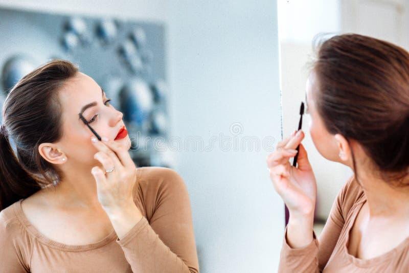Mujer que mira en el espejo que peina sus cejas fotografía de archivo