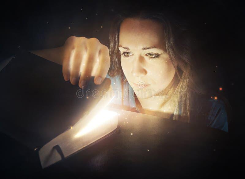 Mujer que mira en la biblia que brilla intensamente. foto de archivo
