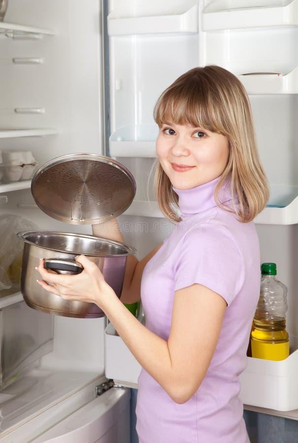 Mujer que mira en la cacerola del refrigerador foto de archivo libre de regalías