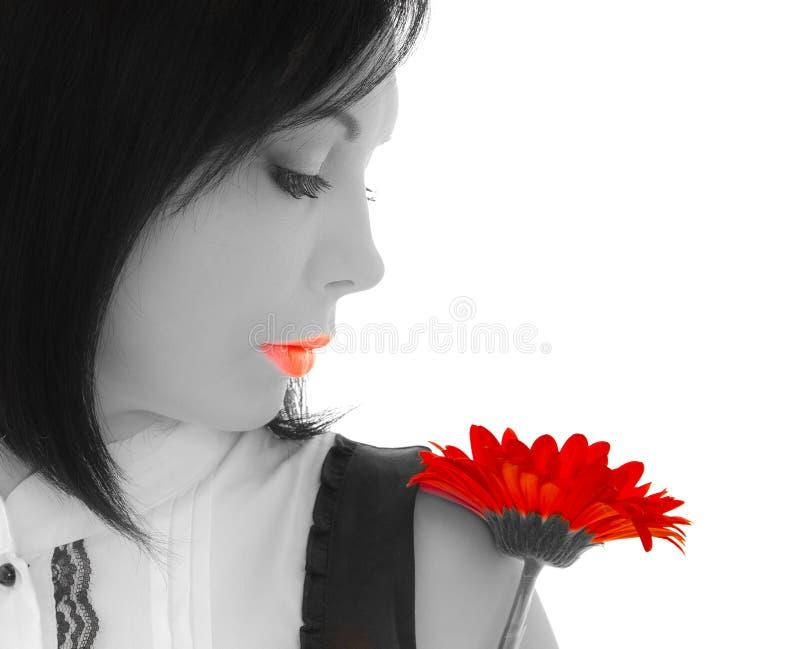 Mujer que mira en la flor roja fotografía de archivo