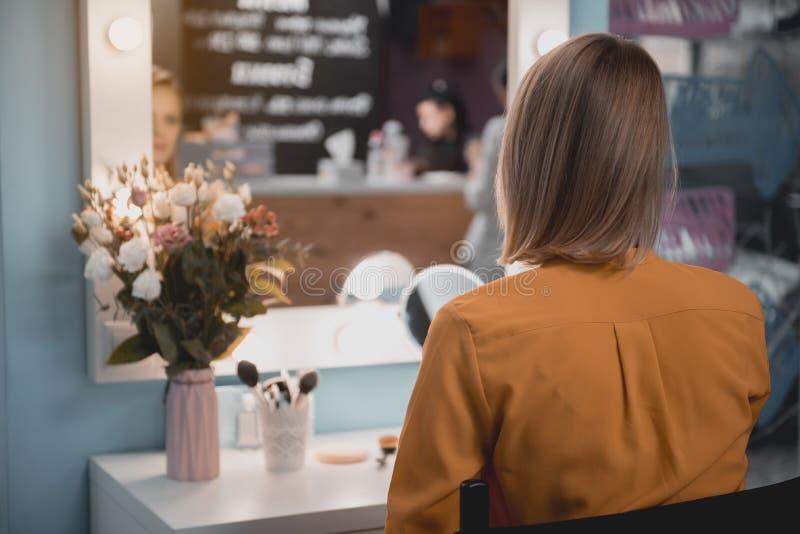 Mujer que mira en la reflexión interior foto de archivo