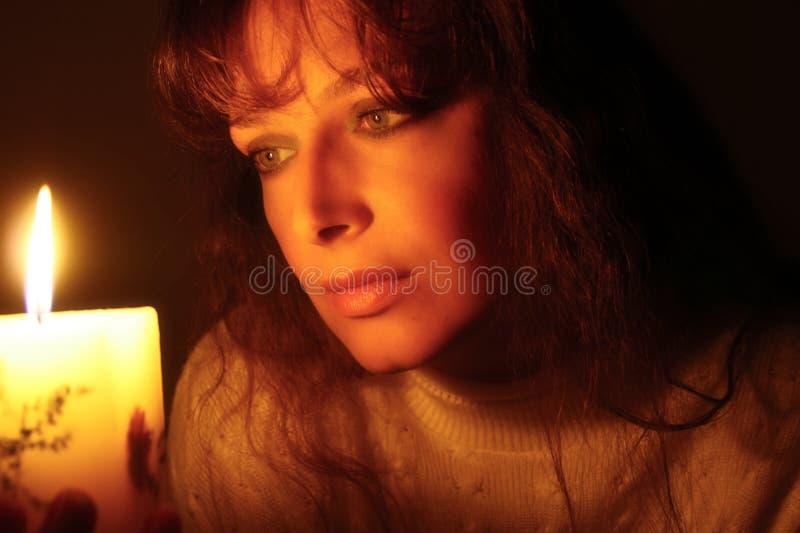 Mujer que mira en luz de una vela fotos de archivo