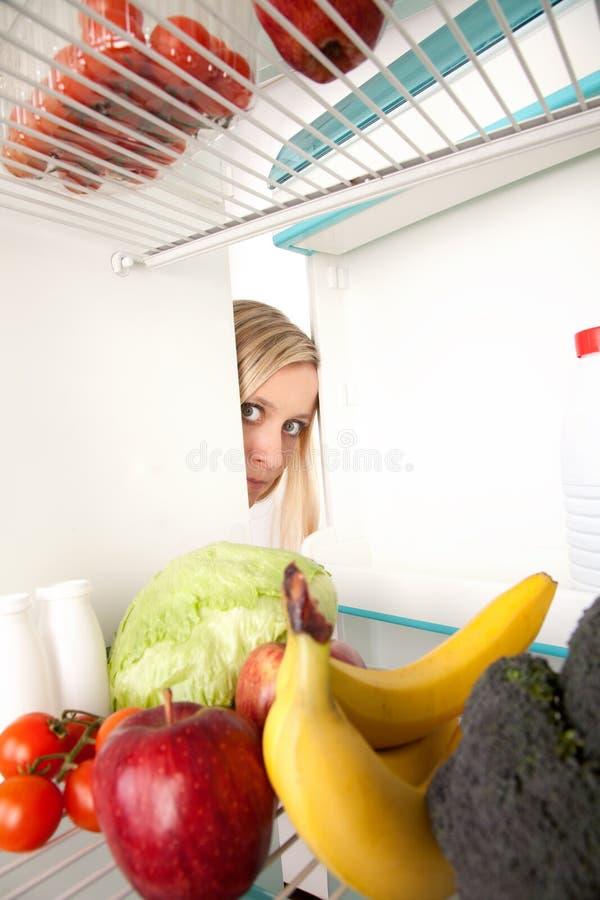 Mujer que mira en refrigerador fotos de archivo