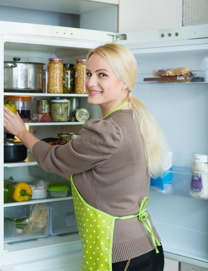 Mujer que mira en refrigerador imagenes de archivo