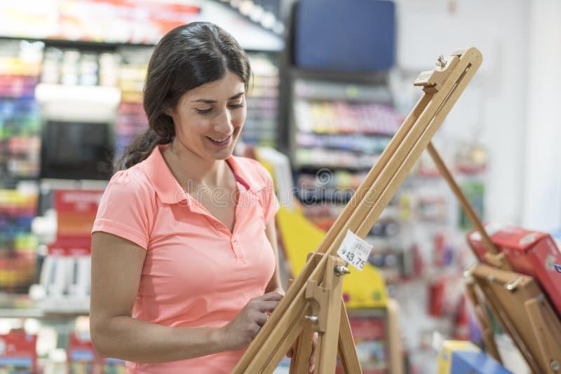 Mujer que mira en tienda una sonrisa del caballete fotos de archivo
