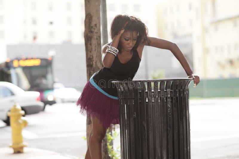 Mujer que mira en un bote de basura imagen de archivo